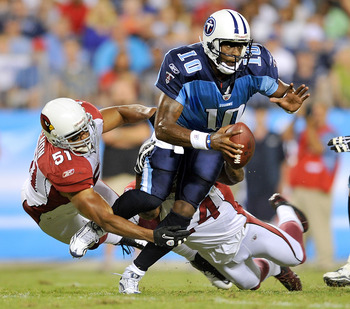NASHVILLE, TN - AUGUST 23:  Vince Young #10 of the Tennessee Titans scrambles away from Paris Lenon #51 and Adrian Wilson #24 of the Arizona Cardinals during the first half of a preseason game at LP Field on August 23, 2010 in Nashville, Tennessee.  (Phot