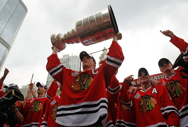CHICAGO - JUNE 11: Jonathan Toews #19 hoists the cup during the Chicago Blackhawks Stanley Cup victory parade and rally on June 11, 2010 in Chicago, Illinois. (Photo by Jonathan Daniel/Getty Images)