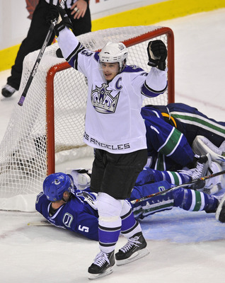 VANCOUVER, CANADA - APRIL 17:  Dustin Brown #23 of the Los Angeles Kings celebrates teammate's Fredrik Modin's #33 (not pictured) goal while Christian Ehrhoff #1 and goalie Roberto Luongo #1 lay on the ice during the second period in Game Two of the Weste