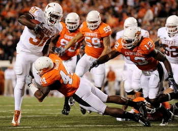 STILLWATER, OK - OCTOBER 31:  Cody Johnson #31 of the Texas Longhorns rushes for five yards short of the endzone and is stopped by Donald Booker #44 of the Oklahoma State Cowboys in the fourth quaretr of the game at Boone Pickens Stadium on October 31, 20