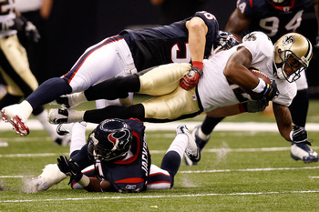 NEW ORLEANS - AUGUST 21:  Marques Colston #12 of the New Orleans Saints is tackled by Brian Cushing #56 and Kareem Jackson #25 of the Houston Texans at the Louisiana Superdome on August 21, 2010 in New Orleans, Louisiana.  (Photo by Chris Graythen/Getty I
