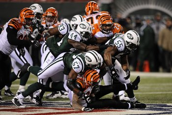 EAST RUTHERFORD, NJ - JANUARY 03:  Bart Scott #57 of the New York Jets takes down Larry Johnson #27 of the Cincinnati Bengals with the help of the defensive line during the second half of the game at Giants Stadium on January 3, 2010 in East Rutherford, N