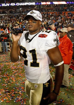 MIAMI GARDENS, FL - FEBRUARY 07:  Mike Bell #21 of the New Orleans Saints video tapes on the field after his team defeated the Indianapolis Colts during Super Bowl XLIV on February 7, 2010 at Sun Life Stadium in Miami Gardens, Florida.  (Photo by Jonathan