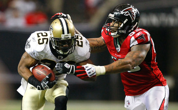 ATLANTA - DECEMBER 13:  Reggie Bush #25 of the New Orleans Saints runs the ball against John Abraham #55 of the Atlanta Falcons at Georgia Dome on December 13, 2009 in Atlanta, Georgia. The Saints won 26-23. (Photo by Kevin C. Cox/Getty Images)