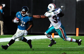JACKSONVILLE, FL - DECEMBER 13:  Maurice Jones-Drew #32 of the Jacksonville Jaguars runs the ball against Yeremiah Bell #37 of the Miami Dolphins during the game at Jacksonville Municipal Stadium on December 13, 2009 in Jacksonville, Florida. The Dolphins