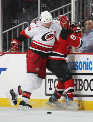 NEWARK, NJ - APRIL 17: Zach Parise #9 of the New Jersey Devils is hit into the boards by Joni Pitkanen #25 of the Carolina Hurricanes during Game Two of the Eastern Conference Quarterfinal Round of the 2009 NHL Stanley Cup Playoffs at the Prudential Cente