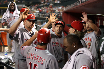 PHOENIX - AUGUST 18:  (L-R) Jonny Gomes #31, Joey Votto #19 and Scott Rolen #27 of the Cincinnati Reds congratulate teammate Jim Edmonds #15 after he scored a run against the Arizona Diamondbacks during the ninth inning of the Major League Baseball game a