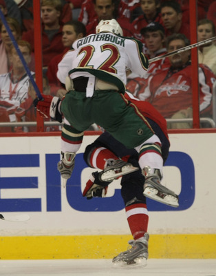 WASHINGTON - NOVEMBER 13: Mike Green #52 of the Washington Capitals is hit by Cal Clutterbuck #22 of the Minnesota Wild at the Verizon Center on November 13, 2009 in Washington, DC.  (Photo by Bruce Bennett/Getty Images)