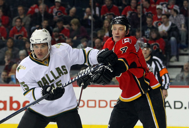 CALGARY, CANADA - FEBRUARY 16:  Jamie Langenbrunner #15 of the Dallas Stars battles for position with Jay Bouwmeester #4  of the Calgary Flames during their NHL game at Scotiabank Saddledome, February 16, 2011 in Calgary, Alberta, Canada. (Photo By Dave S