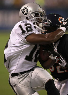 CHICAGO - AUGUST 21: Jacoby Ford #12 of the Oakland Raiders is hit by Kevin Malast #52 of the Chicago Bears during a preseason game at Soldier Field on August 21, 2010 in Chicago, Illinois. The Raiders defeated the Bears 32-17. (Photo by Jonathan Daniel/G