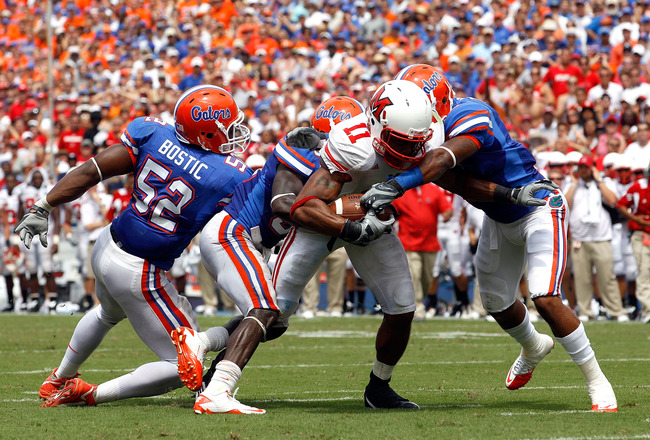 GAINESVILLE, FL - SEPTEMBER 04:  Armand Robinson #11 of the Miami University RedHawks is tackled by Johnathan Bostic #52 and Jeremy Brown #8 of the Florida Gators at Ben Hill Griffin Stadium on September 4, 2010 in Gainesville, Florida.  (Photo by Sam Gre
