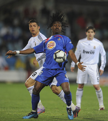GETAFE, SPAIN - MARCH 25:  Derek Boateng (R) of Getafe robs the ball from Cristiano Ronaldo of Real Madrid during La Liga match between Getafe and Real Madrid at the Coliseum Alfonso Perez stadium on March 25, 2010 in Getafe, Spain.  (Photo by Denis Doyle