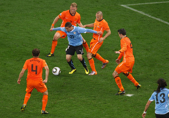 CAPE TOWN, SOUTH AFRICA - JULY 06: Sebastian Fernandez of Uruguay is challenged by the Netherlands defence during the 2010 FIFA World Cup South Africa Semi Final match between Uruguay and the Netherlands at Green Point Stadium on July 6, 2010 in Cape Town