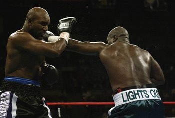 LAS VEGAS - OCTOBER 4:  Evander Holyfield deflects the left-hand punch of James Toney in a heavyweight fight at the Mandalay Bay Casino on October 4, 2003 in Las Vegas, Nevada.  Toney defeated Holyfield by TKO in the ninth round.  (Photo by Jed Jacobsohn/