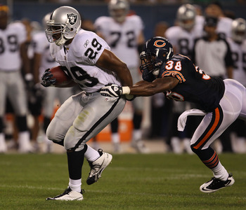 CHICAGO - AUGUST 21: Michael Bush #29 of the Oakland Raiders breaks away from Danieal Manning #38 of the Chicago Bears during a preseason game at Soldier Field on August 21, 2010 in Chicago, Illinois. The Raiders defeated the Bears 32-17. (Photo by Jonath