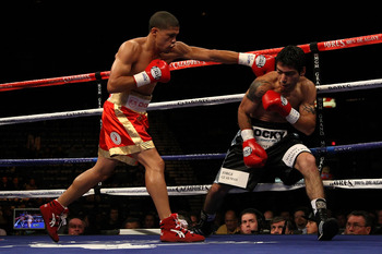 LAS VEGAS - DECEMBER 06:  (L-R) Juan Manuel Lopez of Puerto Rico throws a left to the head of Sergio Medina of Argentina during their WBO junior featherweight title fight at the MGM Grand Garden Arena December 6, 2008 in Las Vegas, Nevada. Lopez knocked o