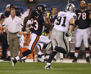 CHICAGO - AUGUST 21: Devin Hester #23 of the Chicago Bears runs after catching a pass as Trevor Scott #91 of the Oakland Raiders pursues during a preseason game at Soldier Field on August 21, 2010 in Chicago, Illinois. The Raiders defeated the Bears 32-17