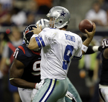 HOUSTON - AUGUST 28: Quarterback Tony Romo #9 of the Dallas Cowboys looks fora receiver as he receives some pressure from defensive tackle Amobi Akoye #91 of the Houston Texans during a football game against the Houston Texans at Reliant Stadium on August