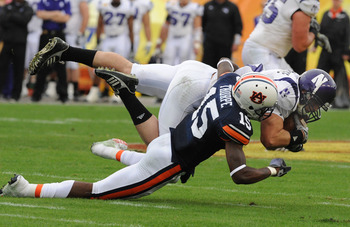 TAMPA, FL - JANUARY 1: Defensive back Neiko Thorpe #15 of the Auburn Tigers tackles split back Drake Dunsmore #9 of the Northwestern Wildcats in the Outback Bowl January 1, 2010 at Raymond James Stadium in Tampa, Florida.  (Photo by Al Messerschmidt/Getty