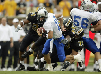 COLUMBIA, MO - SEPTEMBER 13:  Andy Vincent #16 of the Eastern Illinois Panthers runs with the ball as he tries to escape the grasp of C. J. Mosley #99 of the Missouri Tigers on September 13, 2003 at Memorial Stadium in Columbia, Missouri.  Missouri defeat
