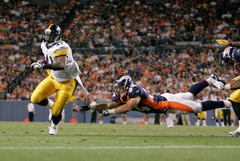 DENVER - AUGUST 29: Running back Jonathan Dwyer #41 of the Pittsburgh Steelers avoids a diving tackle by safety Kyle McCarthy #34 of the Denver Broncos and scores a touchdown in the fourth quarter at INVESCO Field at Mile High on August 29, 2010 in Denver