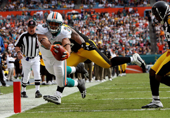 MIAMI - JANUARY 03:  Running back Lex Hilliard #26 of the Miami Dolphins dives for a touchdown past linebacker LaMarr Woodley #56 and Deshea Townsend #26 of the Pittsburgh Steelers at Land Shark Stadium on January 3, 2010 in Miami, Florida.  (Photo by Dou
