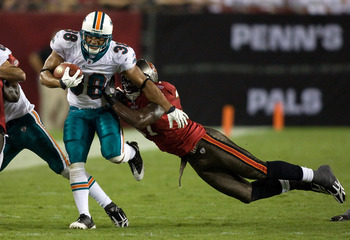 TAMPA, FL - AUGUST 27:  Running back Patrick Cobbs #38 of the Miami Dolphins  is tackled by defender Steve Cargile #37 of the Tampa Bay Buccaneers during a preseason game at Raymond James Stadium on August 27, 2009 in Tampa, Florida.  (Photo by J. Meric/G