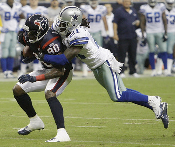 HOUSTON - AUGUST 28:  Wide receiver Andre Johnson #80 of the Houston Texans is tackled from behind by cornerback Mike Jenkins #21 of the Dallas Cowboys in the second quarter in a preseason game at Reliant Stadium on August 28, 2010 in Houston, Texas.  (Ph