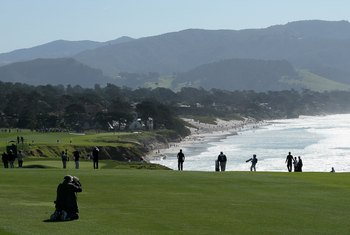 PEBBLE BEACH, CA - FEBRUARY 14:  A photographer lines up a shot on the ninth hole during the final round of the AT&T Pebble Beach National Pro-Am at Pebble Beach Golf Links on February 14, 2010 in Pebble Beach, California.  (Photo by Stephen Dunn/Getty Im