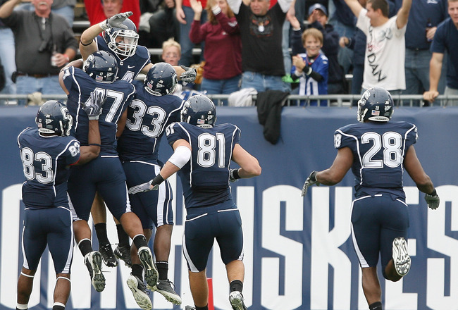 EAST HARTFORD, CT - OCTOBER 31:  Robbie Frey #44 of the Connecticut Huskies is congratulated by teammates Corey Manning #81,Robert Vaughn #33, Anthony Davis #47 and Isiah Moore #83 after Frey returned a kickoff 100 yards for a touchdown in the second quar