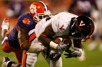 CLEMSON, SC - NOVEMBER 21:  Perry Jones #33 of the Virginia Cavaliers catches a ball as Marcus Gilchrist #12 of the Clemson Tigers tackles him during their game at Memorial Stadium on November 21, 2009 in Clemson, South Carolina.  (Photo by Streeter Lecka
