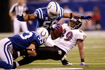 INDIANAPOLIS - JANUARY 16:  Mark Clayton #89 of the Baltimore Ravens is tackled by Melvin Bullitt #33 and Philip Wheeler #50 of the Indianapolis Colts after a catch in the first quarter of the AFC Divisional Playoff Game at Lucas Oli Stadium on January 16