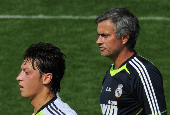 MADRID, SPAIN - AUGUST 19:  New signing Mesut Ozil (L) of Real Madrid runs past his coach Jose Mourinho during a training session at the Valdebebas training ground on August 19, 2010 in Madrid, Spain.  (Photo by Jasper Juinen/Getty Images)