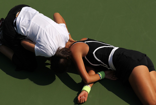 NEW YORK - SEPTEMBER 01:  Victoria Azarenka of Belarus is tended to by medical personnel on the court after she collapsed during her second round women's singles match against Gisela Dulko (seen standing at the bottom of the frame) of Argentina on day thr