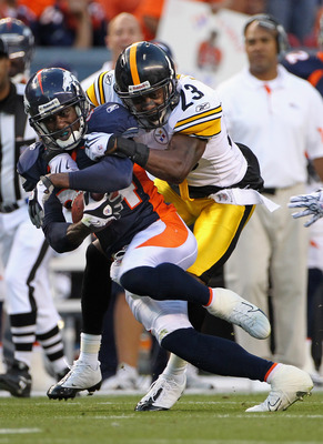 DENVER - AUGUST 29:  Wide Receiver Brandon Lloyd #84 of the Denver Broncos makes a reception and is tackled by cornerback Keenan Lewis #23 of the Pittsburgh Steelers who was called for a personal foul on the play during preseason NFL action at INVESCO Fie
