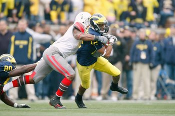 ANN ARBOR, MI - NOVEMBER 21: Roy Roundtree #12 of the Michigan Wolverines tries to get though the tackle of Jermale Hines #7 of the  Ohio State Buckeyes on November 21, 2009 at Michigan Stadium in Ann Arbor, Michigan. Ohio State won the game 21-10. (Photo