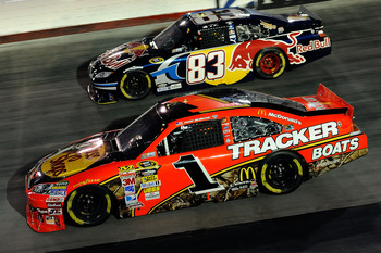 BRISTOL, TN - AUGUST 21:  Jamie McMurray, driver of the #1 Bass Pro Shops/Tracker Boats Chevrolet, and Reen Sorenson, driver of the #83 Red Bull Toyota, race side by side during the NASCAR Sprint Cup Series IRWIN Tools Night Race at Bristol Motor Speedway