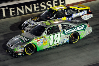 BRISTOL, TN - AUGUST 21:  Kyle Busch, driver of the #18 Doublemint Toyota, and David Reutimann, driver of the #00 Aaron's Dream Machine Toyota, race side by side during the NASCAR Sprint Cup Series IRWIN Tools Night Race at Bristol Motor Speedway on Augus