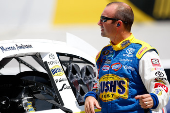 BRISTOL, TN - AUGUST 20: Marcos Ambrose, driver of the #47 Bush's/Kingsford Toyota, stands by his car in the garage area during practice for the NASCAR Sprint Cup Series IRWIN Tools Night Race at Bristol Motor Speedway on August 20, 2010 in Bristol, Tenne