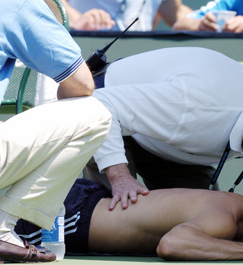 Guillermo Coria  receives treatment from ATP trainer  Bill Norris  then retires after a back injury during the   men's singles match at  the NASDAQ 100 Open, April 4, 2004, Key Biscayne, Florida. (Photo by A. Messerschmidt/Getty Images)