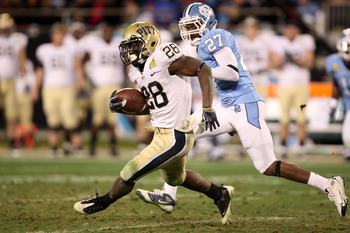 CHARLOTTE, NC - DECEMBER 26:  Dion Lewis #28 of the Pittsburgh Panthers runs away from Deunta Williams #27 of the North Carolina Tar Heels during their game on December 26, 2009 in Charlotte, North Carolina.  (Photo by Streeter Lecka/Getty Images)