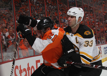 PHILADELPHIA - MAY 12:  Zdeno Chara #33 of the Boston Bruins rides James van Riemsdyk #21 of the Philadelphia Flyers into the boards in Game Six of the Eastern Conference Semifinals during the 2010 NHL Stanley Cup Finals at the Wachovia Center on May 12,