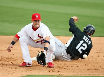 JUPITER, FL - FEBRUARY 25:  Second baseman Skip Schumaker #55 of the St. Louis Cardinals takes the throw as Cody Ross #12 of the Florida Marlins steals second base during a spring training game at Roger Dean Stadium on February 25, 2009 in Jupiter, Florid