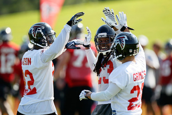 FLOWERY BRANCH, GA - JULY 30:  Chevis Jackson #22, Dunta Robinson #23 and Brent Grimes #20 of the Atlanta Falcons celebrate after a defensive turnover during opening day of training camp on July 30, 2010 at the Falcons Training Complex in Flowery Branch,
