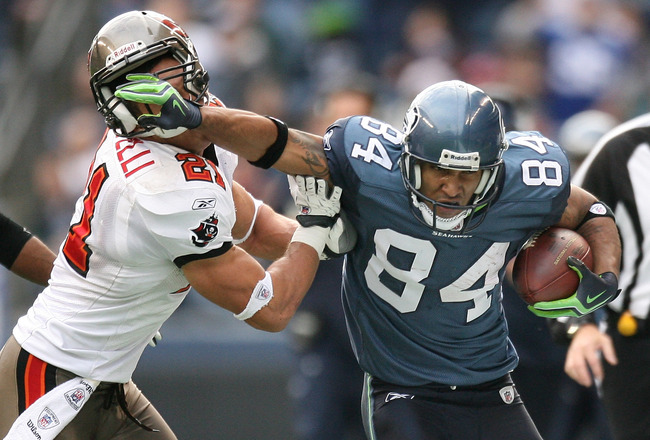 SEATTLE - DECEMBER 20:  Wide receiver T.J. Houshmandzadeh #84 of the Seattle Seahawks straight arms Sabby Piscitelli #21 of the Tampa Bay Buccaneers on December 20, 2009 at Qwest Field in Seattle, Washington. The Buccaneers defeated the Seahawks 24-7.(Pho