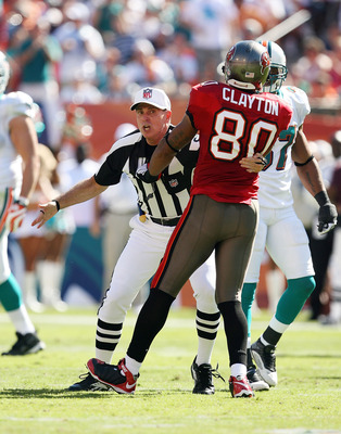 MIAMI GARDENS, FL - NOVEMBER 15:  Referee Tony Corrente #99 tries to seperate wide receiver Michael Clayton #80 of the Tampa Bay Buccaneers from getting into a fight with Dolphin players while taking on the Miami Dolphins at Land Shark Stadium on November