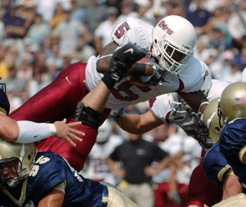 ANNAPOLIS, MD - SEPTEMBER 9:  In this handout provided by the U.S. Navy, running back Steve Baylark of the Massachusetts Minutemen clears a group of Navy Midshipmen defenders to gain yardage in the 1st quarter of play on September 9, 2006 at Navy Memorial