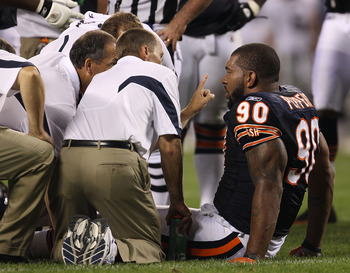 CHICAGO - AUGUST 21: Julius Peppers #90 of the Chicago Bears is attended to by trainers after an injury against the Oakland Raiders during a preseason game at Soldier Field on August 21, 2010 in Chicago, Illinois. The Radiers defeated the Bears 32-17. (Ph