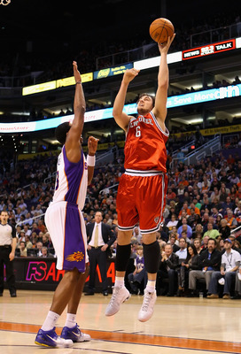 PHOENIX - JANUARY 11:  Andrew Bogut #6 of the Milwaukee Bucks puts up a shot over Channing Frye #8 of the Phoenix Suns during the NBA game at US Airways Center on January 11, 2010 in Phoenix, Arizona. NOTE TO USER: User expressly acknowledges and agrees t