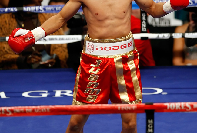 LAS VEGAS - DECEMBER 06:  (L-R) Juan Manuel Lopez of Puerto Rico reacts after knocking out Sergio Medina of Argentina during their WBO junior featherweight title fight at the MGM Grand Garden Arena December 6, 2008 in Las Vegas, Nevada.  (Photo by Ethan M